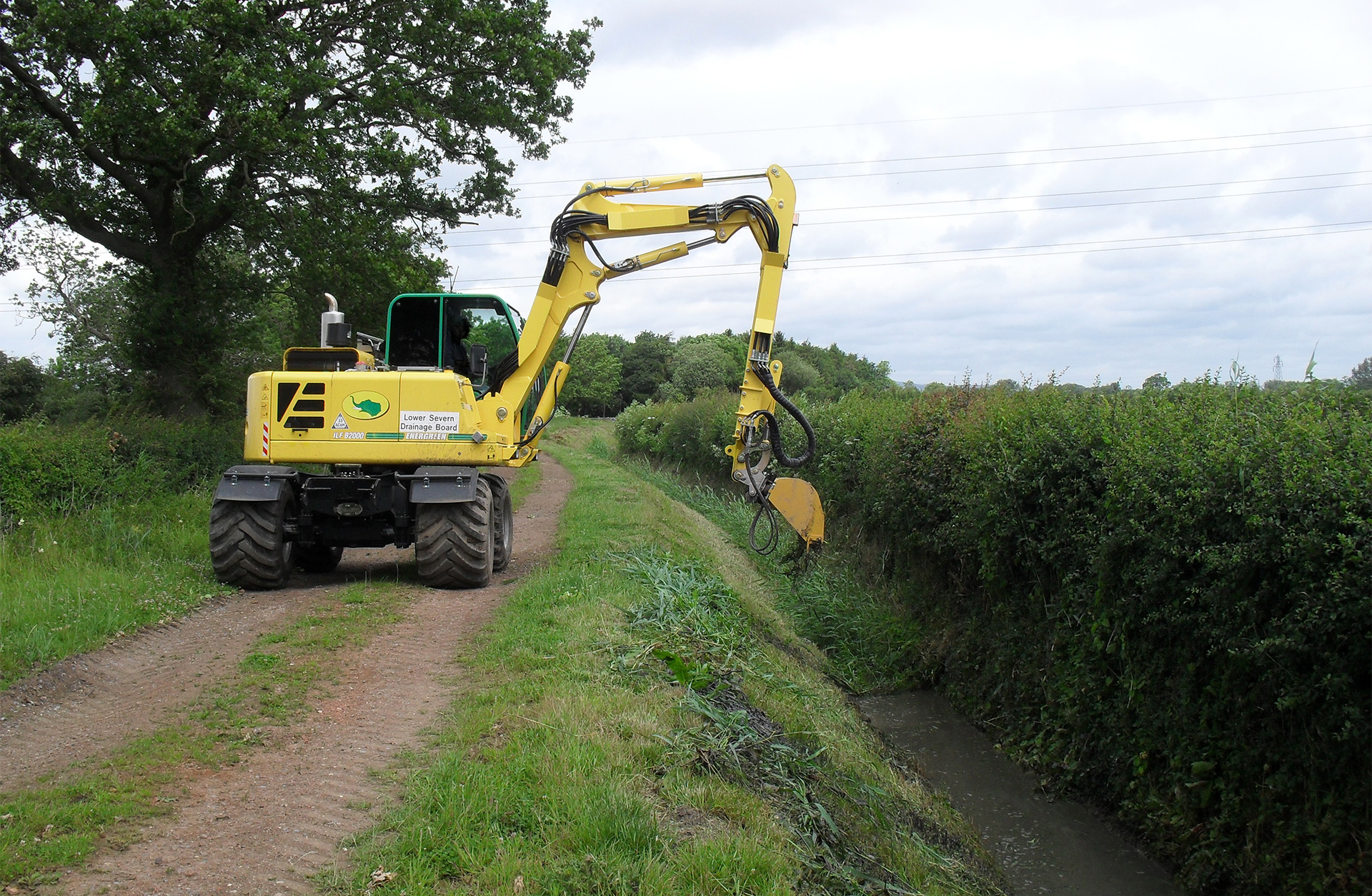 Digger working at roadside ditch